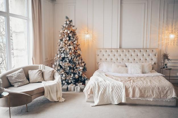 Украшенная елка с подарками в интерьере белой классической спальни