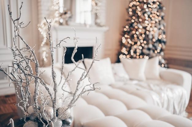 白い古典的な贈り物で飾られたクリスマスツリー