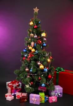 Украшенная елка с подарками на темном цветном фоне