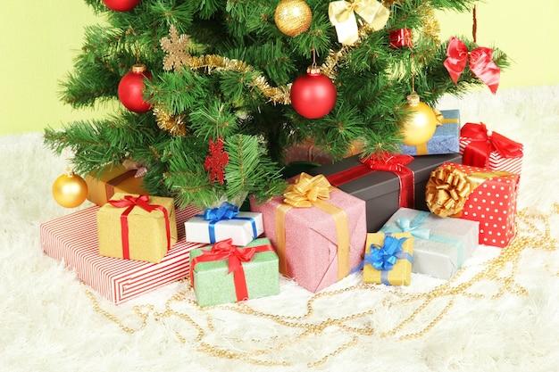 녹색 벽에 선물과 함께 크리스마스 트리 장식
