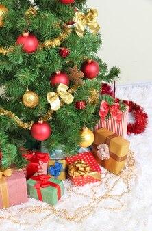 灰色の壁に贈り物で飾られたクリスマスツリー