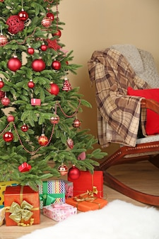 Decorated christmas tree with gifts in room closeup