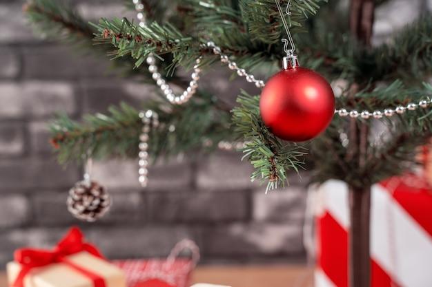 黒レンガの壁と自宅で包まれた美しい赤と白の贈り物で飾られたクリスマスツリー