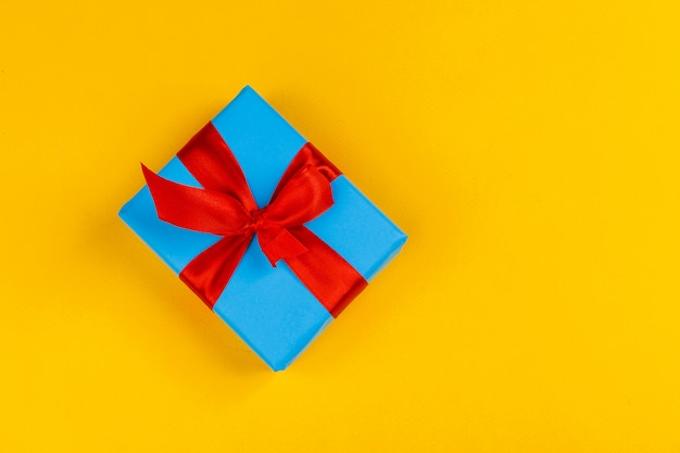 Decorated colored present on yellow background flatlay