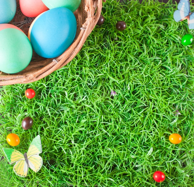 Decorated colorful easter eggs in a basket on the grass. top view. copy space.