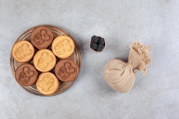 Украшенное печенье на деревянной доске рядом с мешком и небольшой миской тутовых ягод на мраморном фоне. фото высокого качества