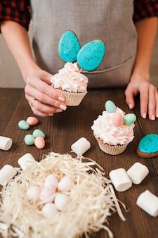 木製のテーブルでイースターのお祝いのための小さな白い卵で飾られたカップケーキと巣