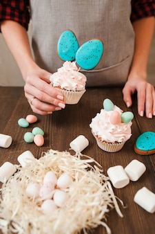 Decorated cup cakes and nest with small white eggs for easter celebration on wooden table