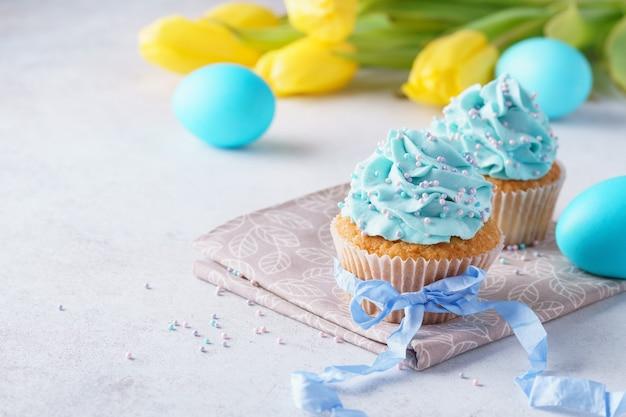イースターのためのクリーム、青い卵とチューリップで飾られたカップケーキ。