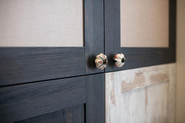 装飾されたドアハンドル。デザイナーキャビネットのマットな黒と白のドアの装飾的な彫刻が施されたハンドル