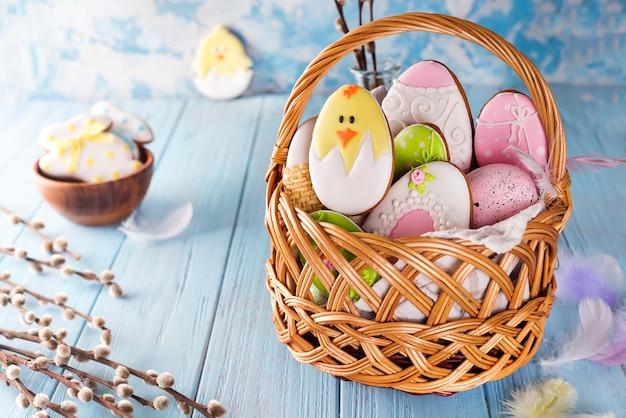 Украшенные пасхальные печенья в деревянной корзине на синем деревянном фоне