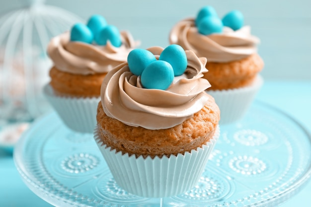 Украшенные пасхальные кексы на подставке для торта на размытом фоне