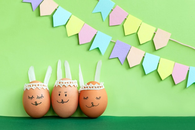 Decorated easter egg and cute bunny's ears with colorful flags on green background