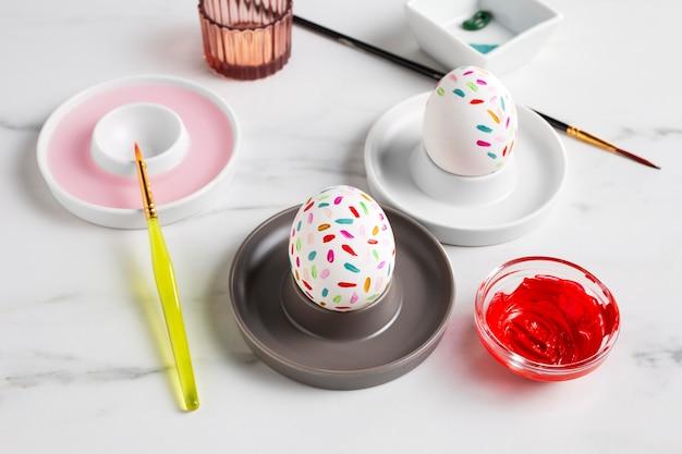 페인트와 붓으로 접시에 부활절 달걀 장식