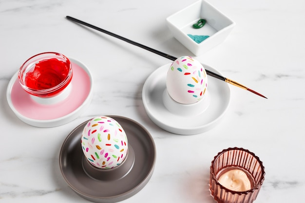 Украшенное пасхальное яйцо на тарелке с кистью и краской
