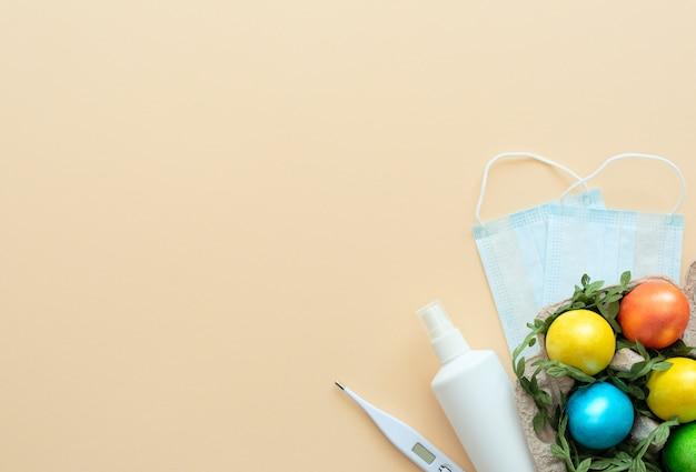 Украшенные пасхальные яйца лежат в картонной коробке на желтом фоне с медицинским термометром для маски для лица и дезинфицирующим средством.