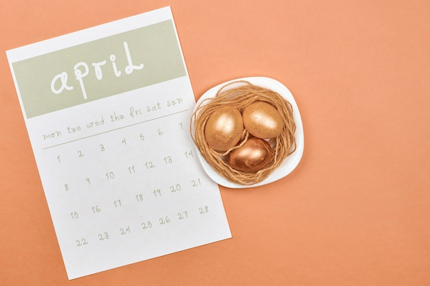 4月のカレンダーで飾られたイースターエッグ。明るい4月の月間カレンダーと金色のイースターのお祝いの卵