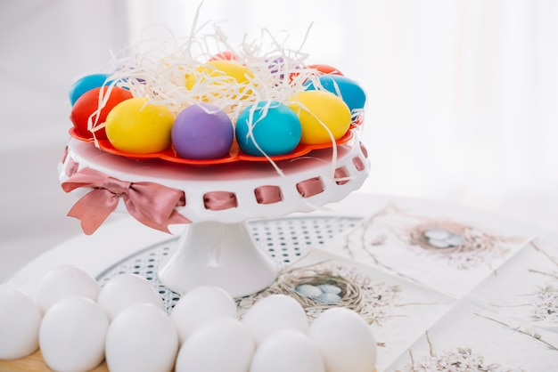 Decorated easter eggs with shredded papers on cakestand over the table