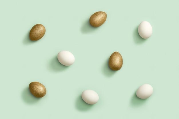 飾られたイースターの金と白の卵。ハッピーイースターパターン。