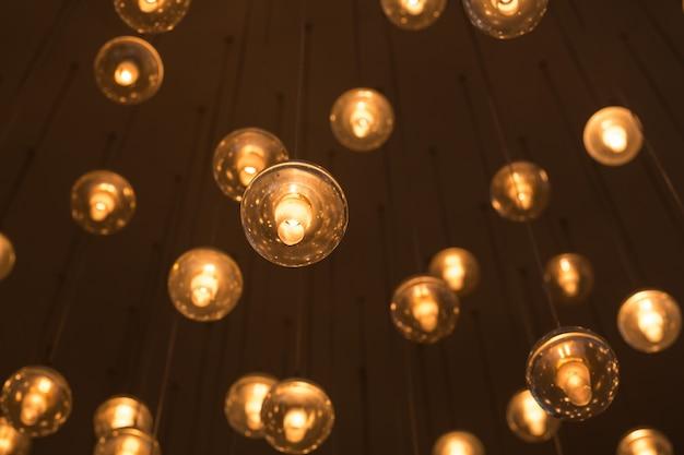 暗いぼやけた上に電球の白と黄色の光を暖める照明用の装飾された電気花輪。インテリアの電球。