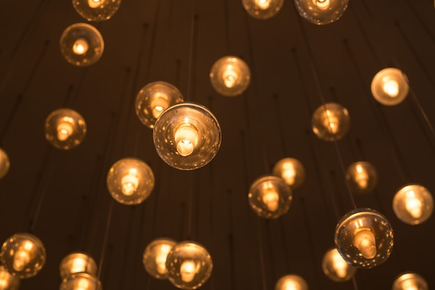 Decorated electric garland for lighting with bulbs warm white and yellow light on a dark  blurred . bulbs in the interior decor.