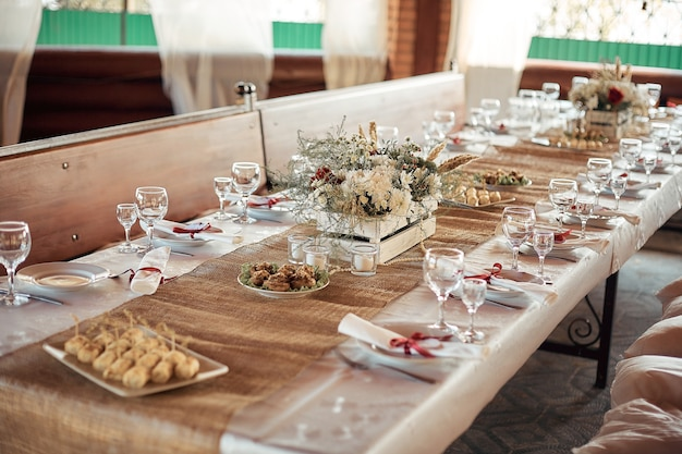 Decorated elegant wooden wedding table for banquet outdoor in garden gazebo