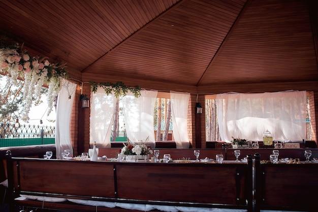 Украшенный элегантный деревянный свадебный стол для банкета на открытом воздухе в садовой беседке