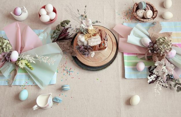 디저트, 계란 및 꽃으로 장식 된 축제 테이블. 행복 한 부활절 개념입니다.