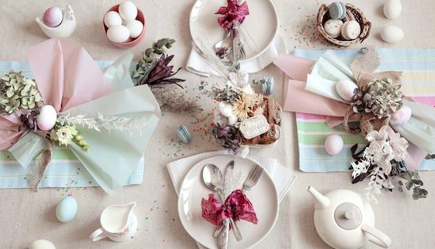 イースターのデザート、お茶、卵を平らに置いた装飾されたお祝いのテーブル。ハッピーイースターのコンセプト。