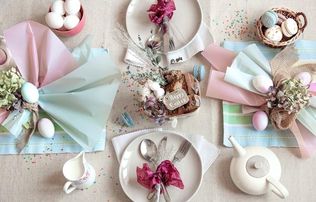 부활절 디저트, 차, 계란이 깔린 축제 테이블 장식. 행복 한 부활절 개념입니다.