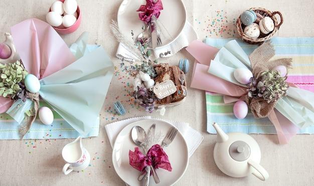 부활절 디저트, 차, 계란이 깔린 축제 테이블 장식. 행복 한 부활절 개념입니다. 프리미엄 사진
