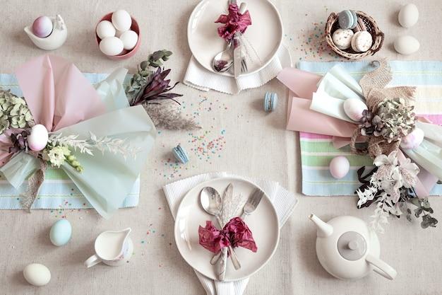 Tavola festiva decorata con dessert pasquale, tè e uova piatte. felice pasqua concetto.