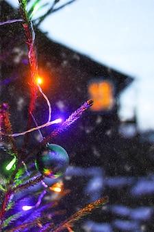 カントリーハウスの背景に屋外で飾られたモミの木。冬の休日のお祭りの背景。