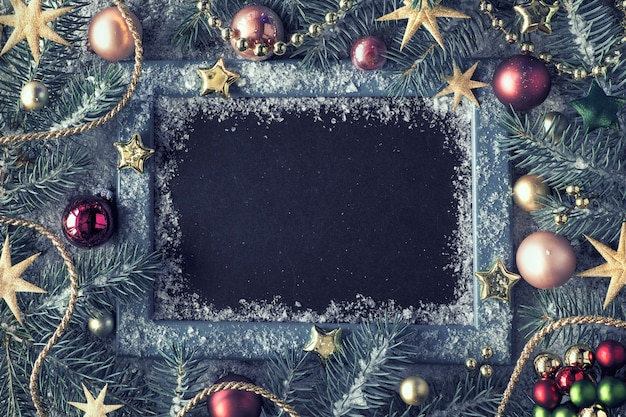 Decorated fir twigs around chalk board on rustic wood with snow. top view with copy space.