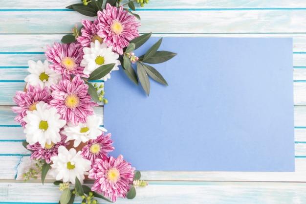 나무 테이블 위에 빈 종이에 꽃 디자인 장식