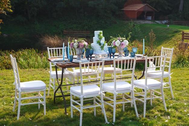 庭のエレガントなディナーテーブルの結婚式のために飾られました