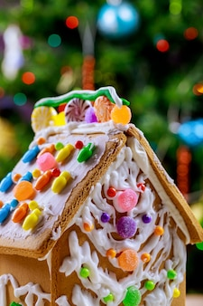 Decorated gingerbread house in front of a christmas tree.