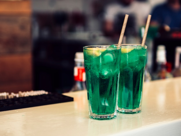 Decorated glasses of colourful green beverage
