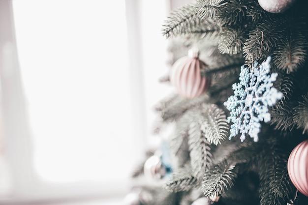 창 근처 녹색 크리스마스 트리 장식. 내부 일광. 장식용 화려한 장난감. 사람이없는 빈 방.