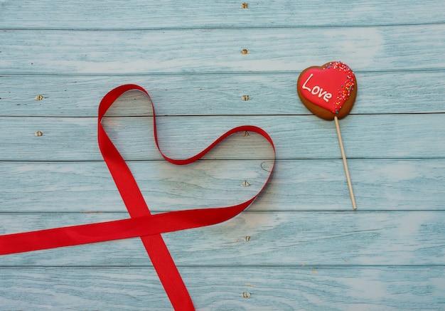 Украшенное печенье в форме сердца на палочке с красной лентой в форме сердца на синем деревянном фоне. место для текста. день святого валентина концепции. любить