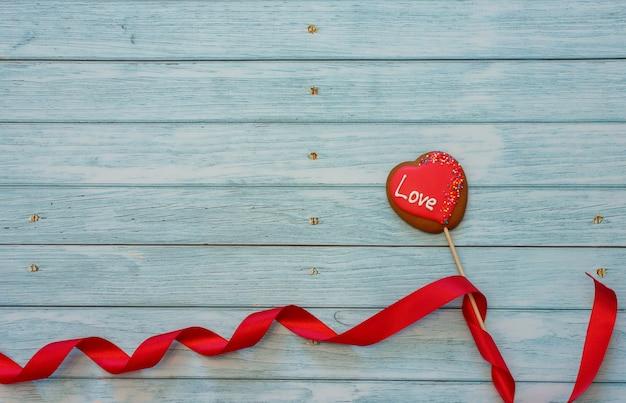 Украшенное печенье в форме сердца на палочке с красной лентой на синем деревянном фоне. место для текста. день святого валентина концепции. любить