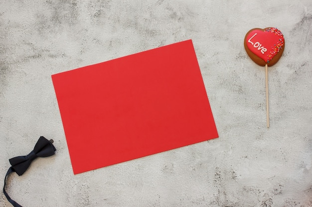 Украшенное печенье в форме сердца и галстук-бабочку на красном листе для текста. место для текста. день святого валентина концепции. карта