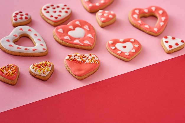Decorated heart shape cookies on colored red and pink background, top view