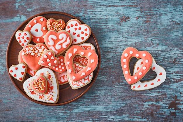 Украшенное печенье в форме сердца в белой тарелке и два печенья на сером, вид сверху