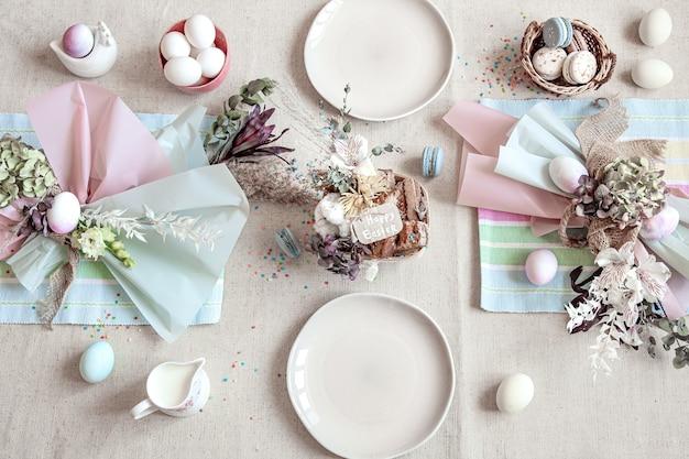 하얀 접시, 계란, 꽃꽂이로 장식 된 휴일 테이블. 행복 한 부활절 개념입니다.
