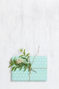 ターコイズブルーの紙の誕生日プレゼントに庭の木の枝と木製の背景の花で飾られました
