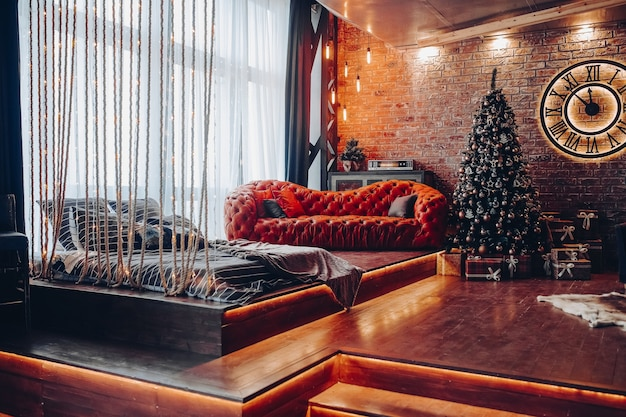 크리스마스 인테리어 장식. 현대 비싼 소파와 로마 숫자와 함께 큰 시계 근처 아름 다운 크리스마스 트리.