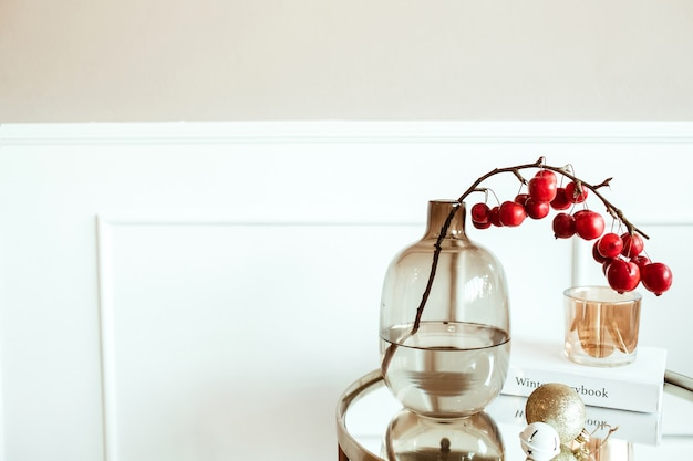 Decorated living room. bedside table with red berries bouquet in glass vase, book, candle in front of beige wall