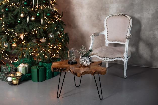 アームチェア木製コーヒーテーブルとギフト付きのクリスマスツリーで飾られたリビングルームのロフトのインテリア