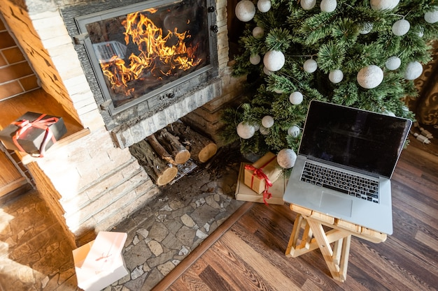 Decorated for new year room no people laptop with small gift boxes close-up in an old wooden house